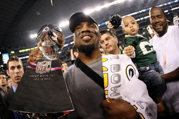 ARLINGTON, TX - FEBRUARY 06:  Charles Woodson #21 of the Green Bay Packers, who was injured during the game, celebrates with the Vince Lombardi Trophy after they defeated the Pittsburgh Steelers 31 to 25 in Super Bowl XLV at Cowboys Stadium on February 6,
