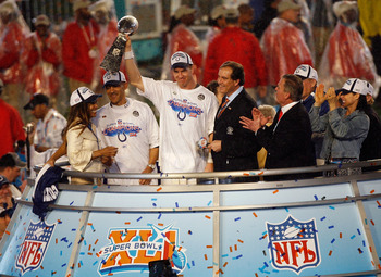 MIAMI GARDENS, FL - FEBRUARY 04:  Quarterback Peyton Manning #18 of the Indianapolis Colts celebrates with the Vince Lombardi Super Bowl trophy next to head coach Tony Dungy and is wife, Lauren, CBS sports broadcaster Jim Nantz and Team owner Jim Irsay af