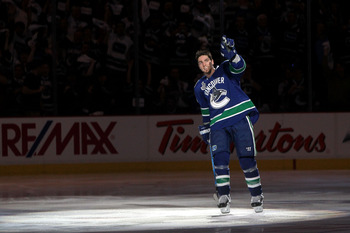 VANCOUVER, BC - JUNE 04:  Alex Burrows #14 of the Vancouver Canucks points to the crowd as he skates off the ice after scoring a goal in overtime against Zdeno Chara #33 and Tim Thomas #30 of the Boston Bruins to win Game Two of the 2011 NHL Stanley Cup F