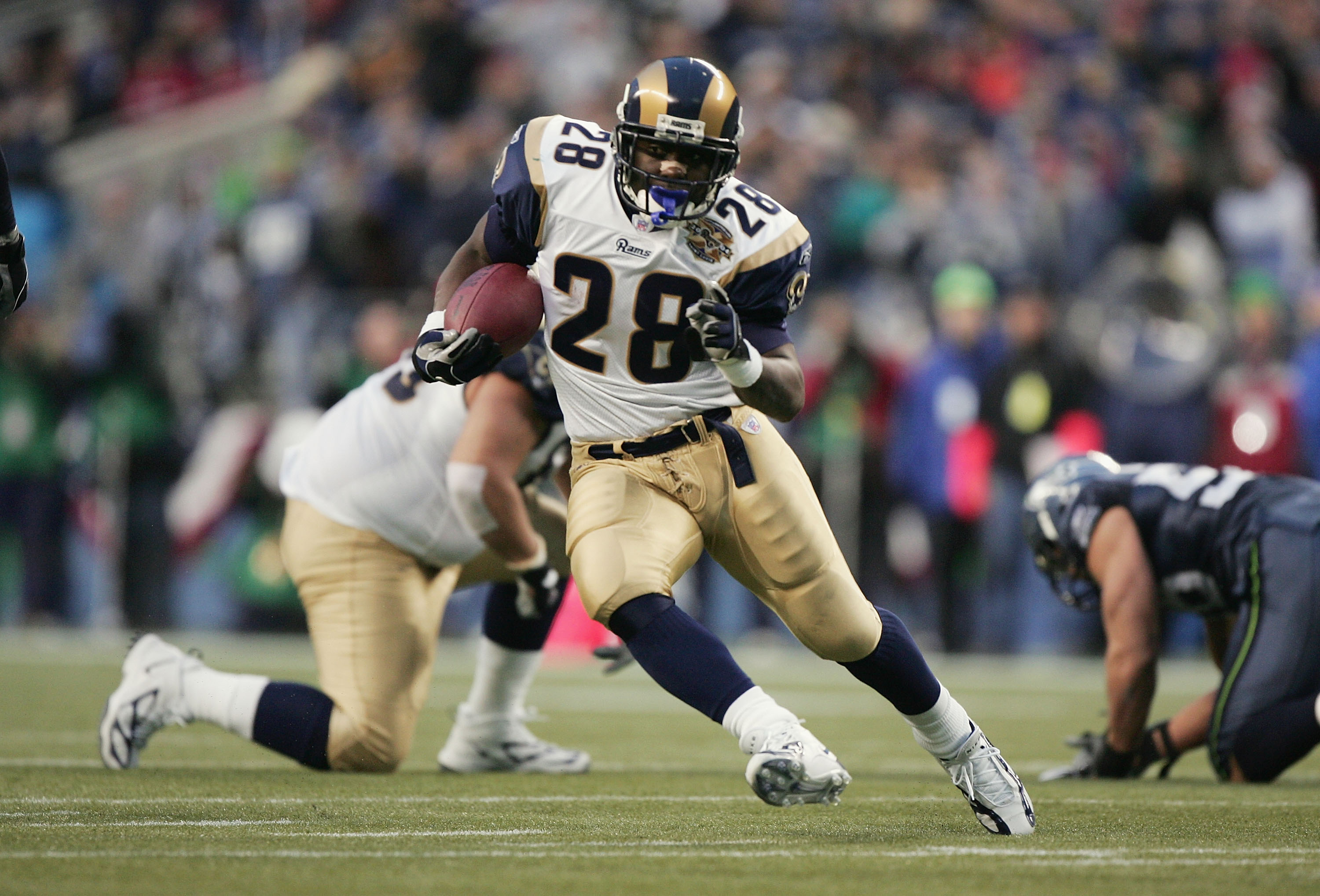 SEATTLE - JANUARY 8: Running back Marshall Faulk #28 of the St. Louis Rams looks for room to run against the Seattle Seahawks in the NFC wild-card game at Qwest Field on January 8, 2005 in Seattle, Washington. The Rams defeated the Seahawks 27-20. (Photo
