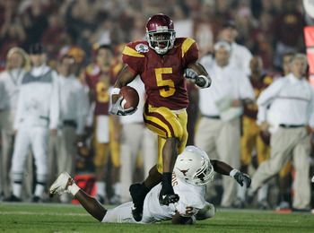PASADENA, CA - JANUARY 04:  Running back Reggie Bush #5 of the USC Trojans carries the football past Aaron Harris #2 of the Texas Longhorns before fumbling the ball on the play in the second quarter during the BCS National Championship Rose Bowl Game on J