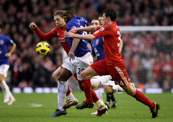 LIVERPOOL, ENGLAND - JANUARY 16:  Lucas (L) and Martin Kelly of Liverpool battle for the ball with Victor Anichebe of Everton during the Barclays Premier League match between Liverpool and Everton at Anfield on January 16, 2011 in Liverpool, England. (Pho