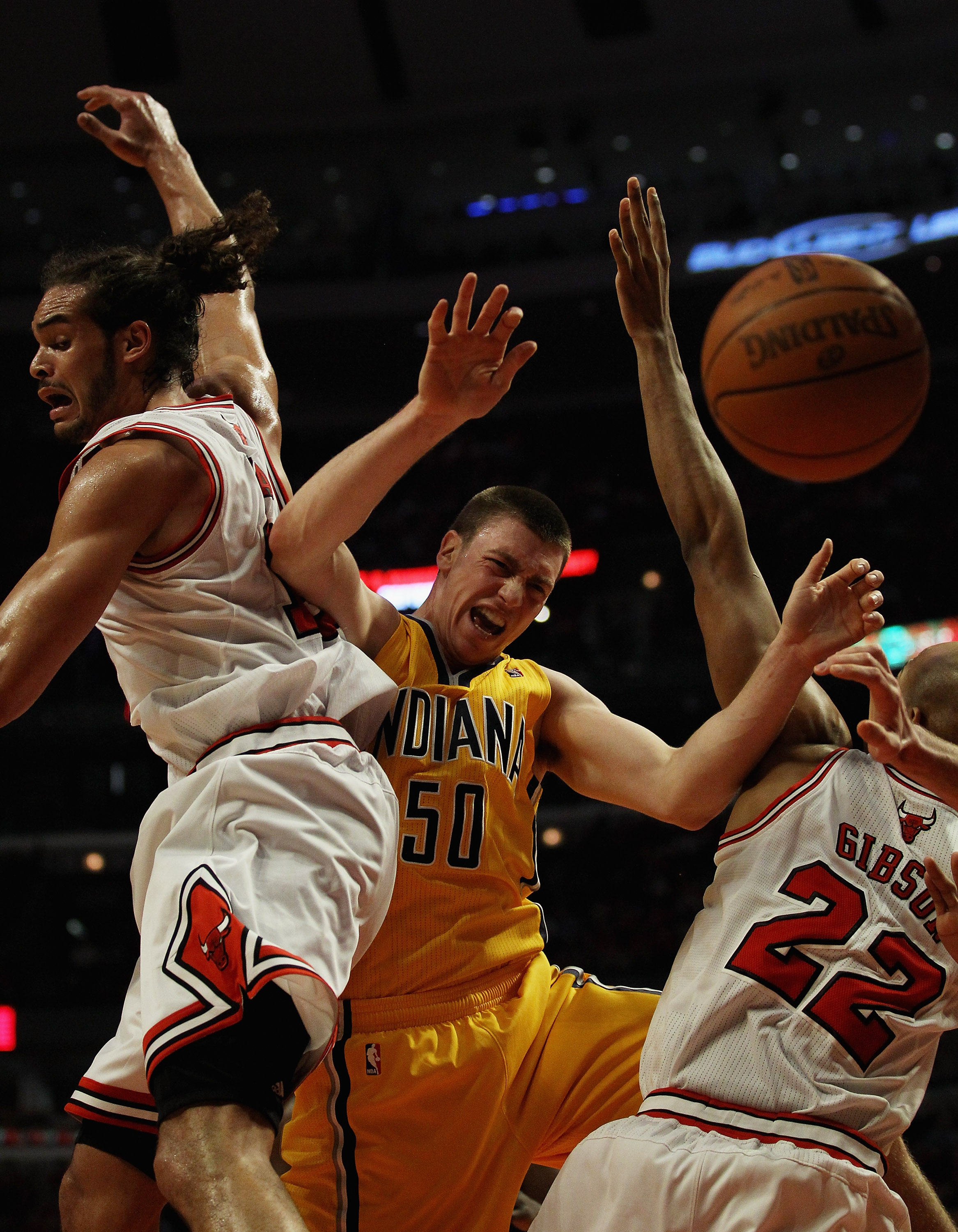 CHICAGO, IL - APRIL 26: Tyler Hansbrough #50 of the Indiana Pacers looses control of the ball under pressure from Joakim Noah #13 and Taj Gibson #22 of the Chicago Bulls in Game Five of the Eastern Conference Quarterfinals in the 2011 NBA Playoffs at the