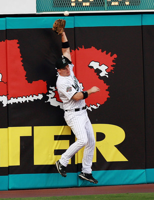 MIAMI - JUNE 22:  Left fielder Josh Willingham #14 of the Florida Marlins can't catch a first inning RBI double by Justin Morneau #33 of the Minnesota Twins during interleague play at Dolphin Stadium on June 22, 2007 in Miami, Florida. The Marlins defeate