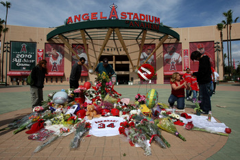 ANAHEIM, CA - APRIL 9:  Fans gather around a makeshift memorial to Los Angeles Angels of Anaheim pitcher Nick Adenhart outside Angel Stadium April 9, 2009 in Anaheim, California. Adenhart and two others were killed in car crash early this morning.  (Photo