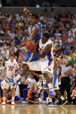 TAMPA, FL - MARCH 19:  Erving Walker #11 of the Florida Gators fights to control the ball against Malcolm Lee #3 of the UCLA Bruins during the third round of the 2011 NCAA men's basketball tournament at St. Pete Times Forum on March 19, 2011 in Tampa, Flo