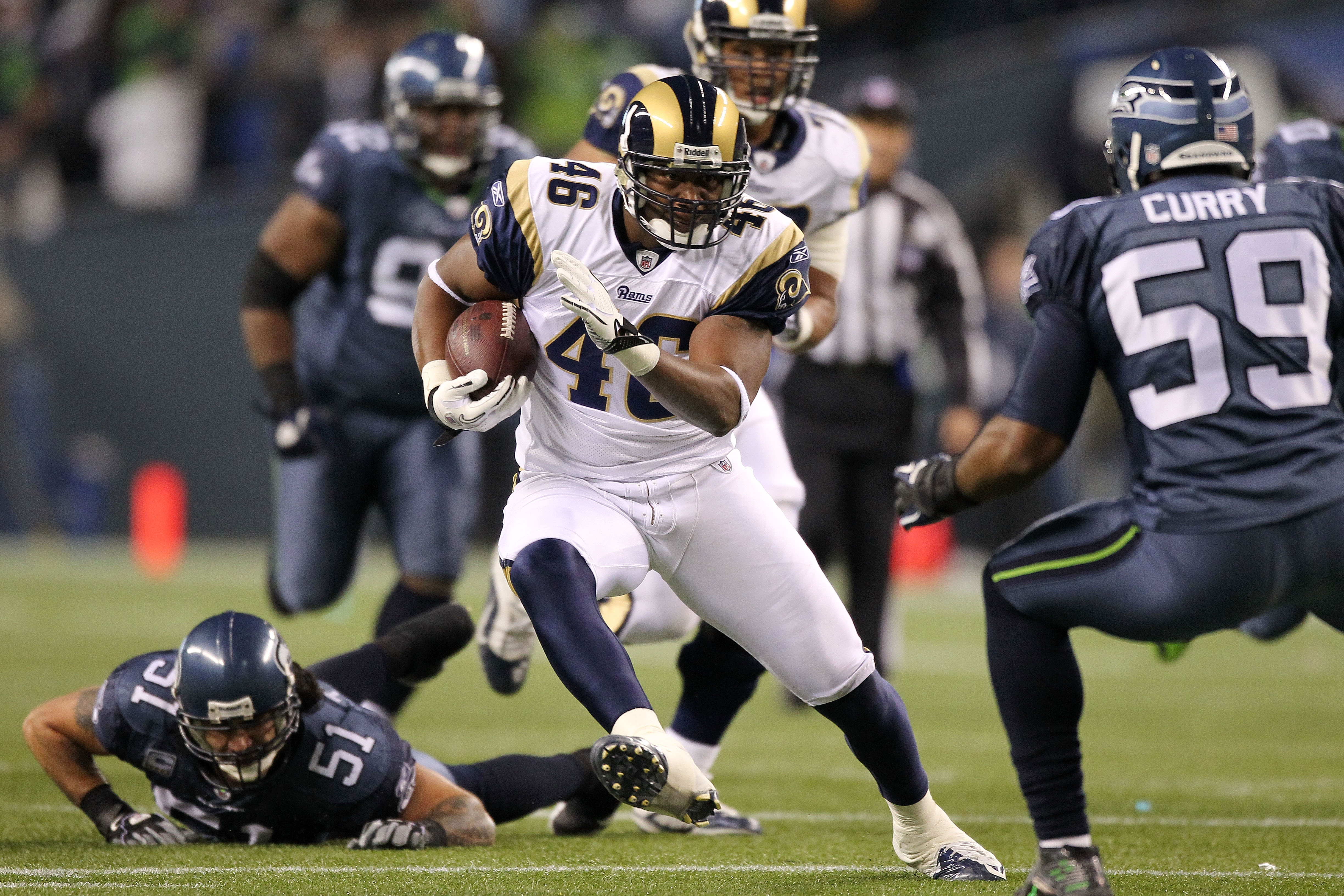 SEATTLE, WA - JANUARY 02:  Tight end Daniel Fells #46 of the St. Louis Rams runs with the ball after a catch as linebacker Aaron Curry #59 of the Seattle Seahawks defends during their game at Qwest Field on January 2, 2011 in Seattle, Washington.  (Photo