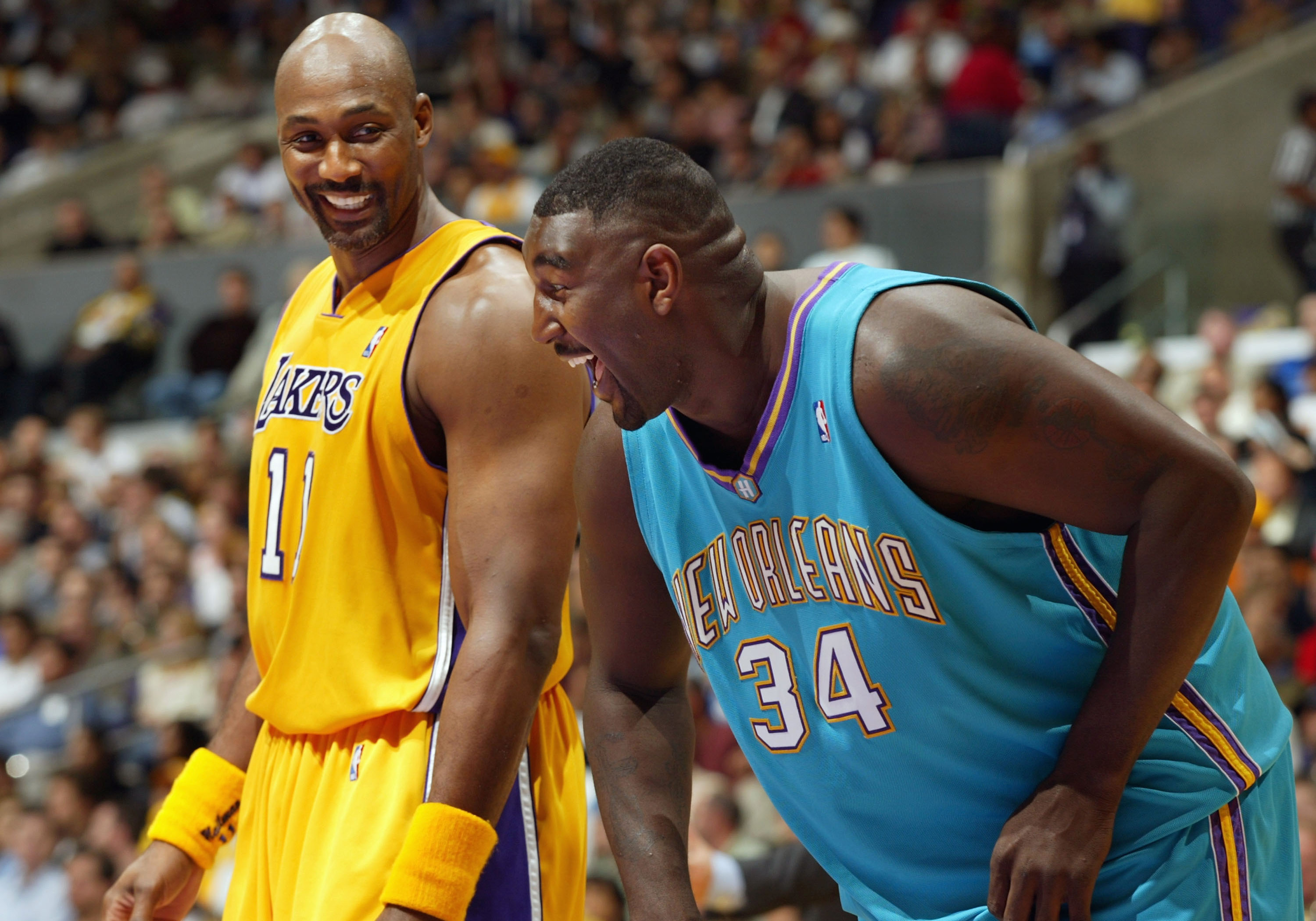 LOS ANGELES - MARCH 30:  Karl Malone #11 of the Los Angeles Lakers shares a laugh with Robert Traylor #34 of the New Orleans Hornets during the game at Staples Center on March 30, 2004 in Los Angeles, California.  NOTE TO USER: User expressly acknowledges