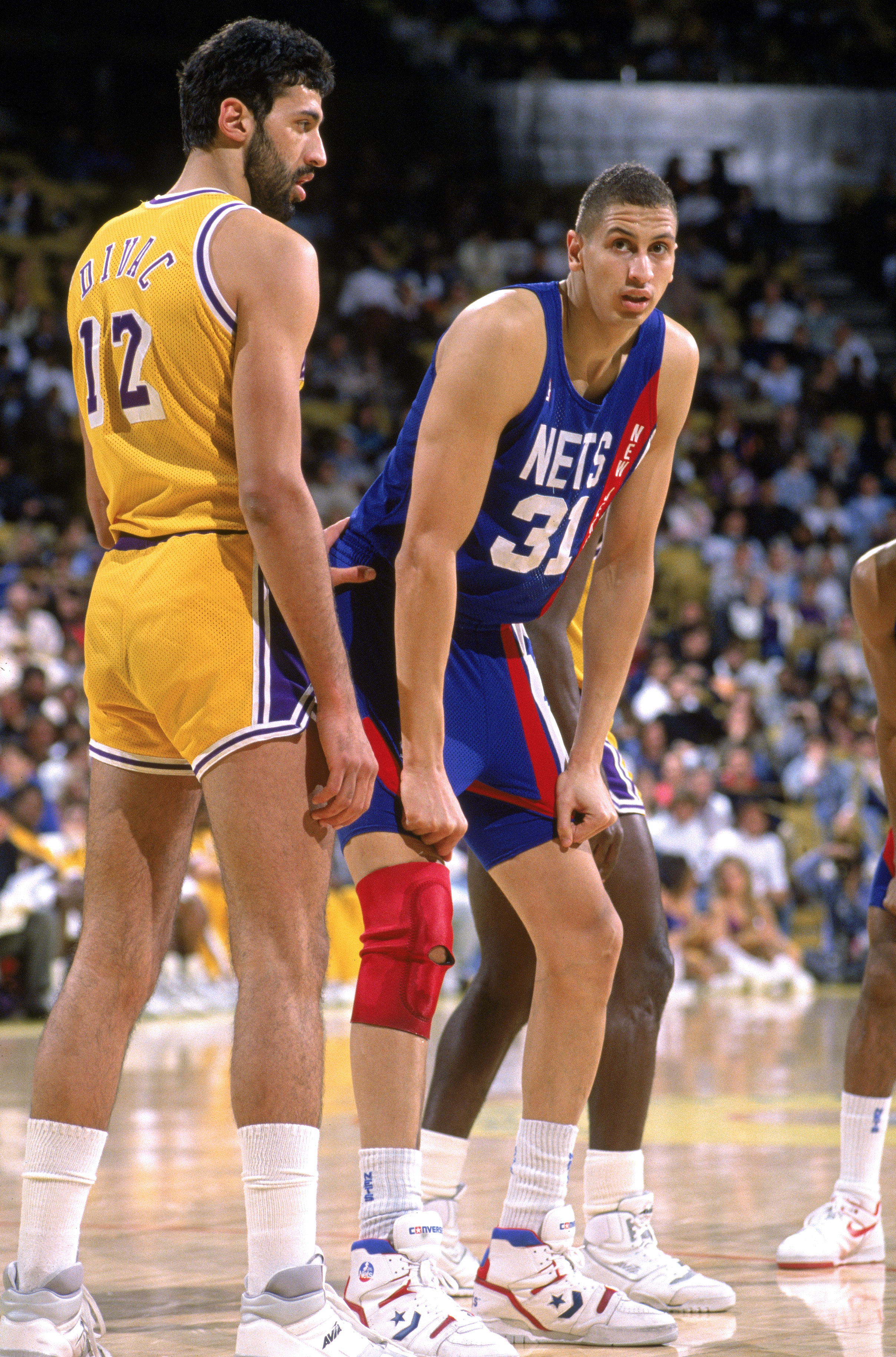 LOS ANGELES - 1990:  Sam Bowie #31 of the New Jersey Nets stands ready for play next to Vlade Divac #12 of the Los Angeles Lakers during the NBA game at the Great Western Forum in Los Angeles, California in 1990. NOTE TO USER: User expressly acknowledges