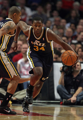 CHICAGO, IL - MARCH 12: C.J. Miles #34 of the Utah Jazz moves up the court past teammate Earl Watson #11 against the Chicago Bulls at the United Center on March 12, 2011 in Chicago, Illinois. The Bulls defeated the Jazz 118-100. NOTE TO USER: User express