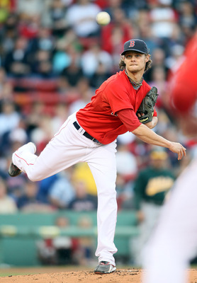 BOSTON, MA - JUNE 03:  Clay Buchholz #11 of the Boston Red Sox sends the ball to first to try and pick of David DeJesus of the Oakland Athletics on June 3, 2011 at Fenway Park in Boston, Massachusetts.  (Photo by Elsa/Getty Images)