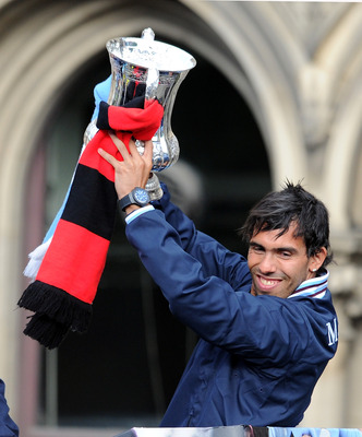 MANCHESTER, ENGLAND - MAY 23: Carlos Tevez of Manchester City lifts the FA Cup during the Manchester City FA Cup Winners Parade at Manchester Town Hall on May 23, 2011 in Manchester, United Kingdom.  (Photo by Chris Brunskill/Getty Images)