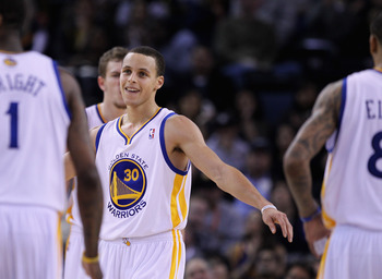 OAKLAND, CA - MARCH 25:  Stephen Curry #30 of the Golden State Warriors congratulates his teammates during their game against the Toronto Raptors at Oracle Arena on March 25, 2011 in Oakland, California. NOTE TO USER: User expressly acknowledges and agree