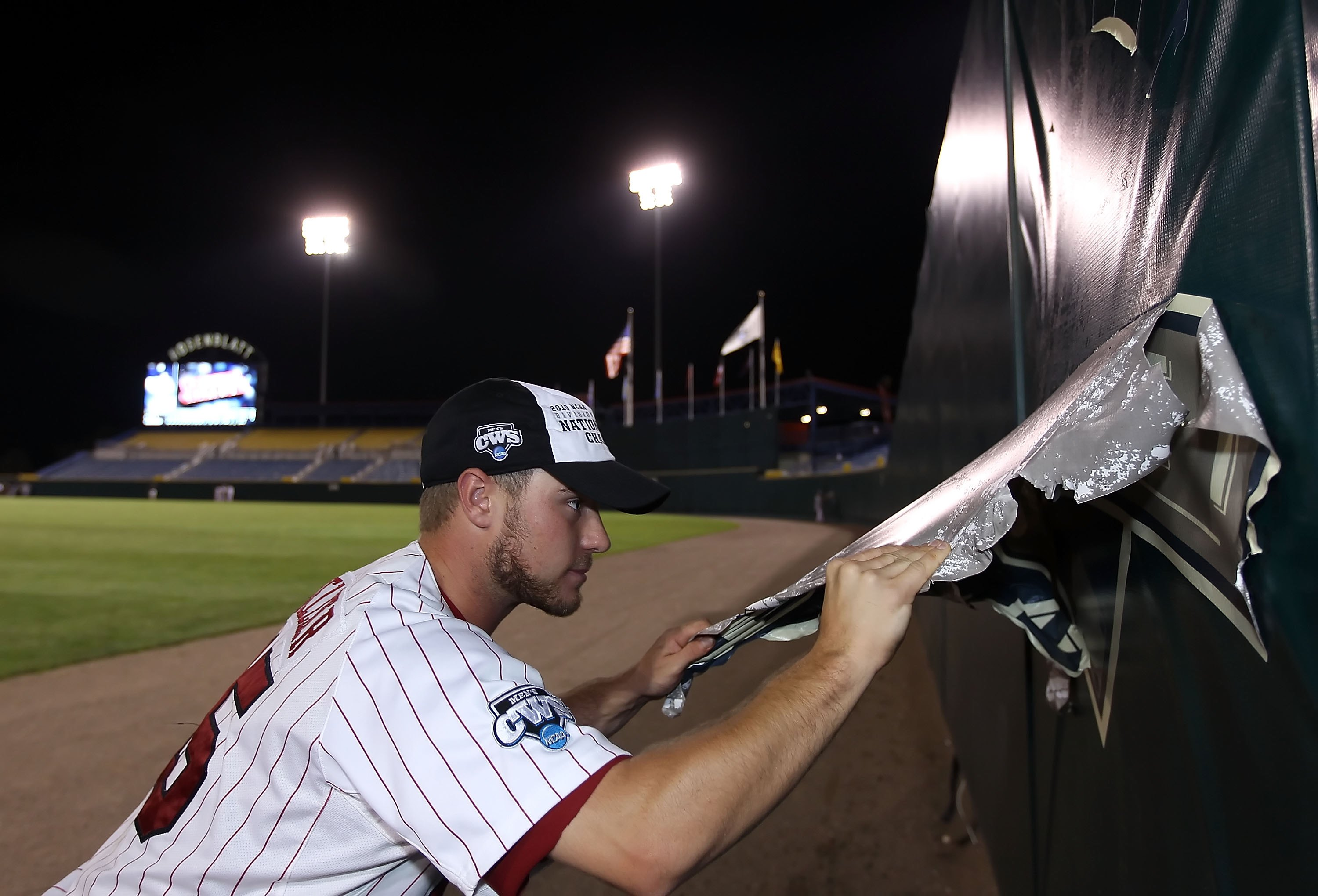 OMAHA, NE - JUNE 29:  Nolan Belcher #15 of the South Carolina Gamecocks tears down a logo from the outfield wall after defeating the UCLA Bruins in game 2 of the men's 2010 NCAA College Baseball World Series at Rosenblatt Stadium on June 29, 2010 in Omaha