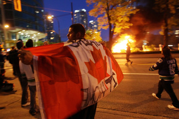 VANCOUVER, BC - JUNE 15:  A person with a Candanian flag walks in front of a burning vehicle on June 15, 2011 in Vancouver, Canada. Vancouver broke out in riots after their hockey team the Vancouver Canucks lost in Game Seven of the Stanley Cup Finals.  (