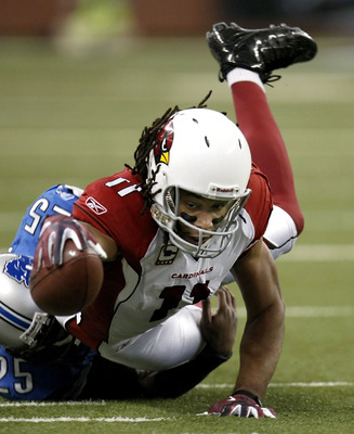DETROIT, MI - DECEMBER 20: Larry Fitzgerald #11 of the  Arizona Cardinals reaches for a first down while being tackled by Marvin White #25 of the Detroit Lions on December 20, 2009 at Ford Field in Detroit, Michigan.  (Photo by Gregory Shamus/Getty Images