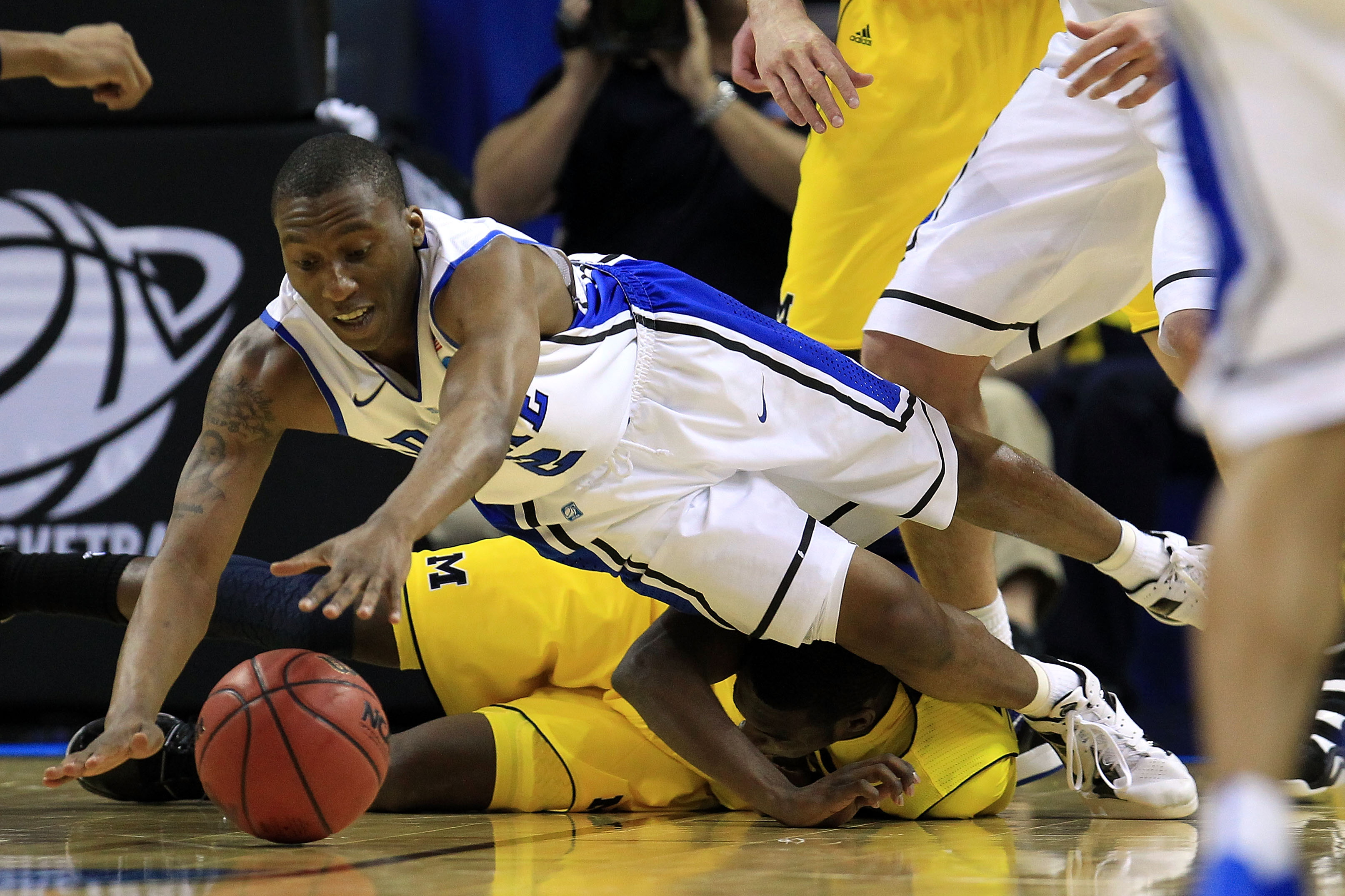 CHARLOTTE, NC - MARCH 20:  Nolan Smith #2 of the Duke Blue Devils dives for the ball over Tim Hardaway Jr. #10 of the Michigan Wolverines in the first half during the third round of the 2011 NCAA men's basketball tournament at Time Warner Cable Arena on M