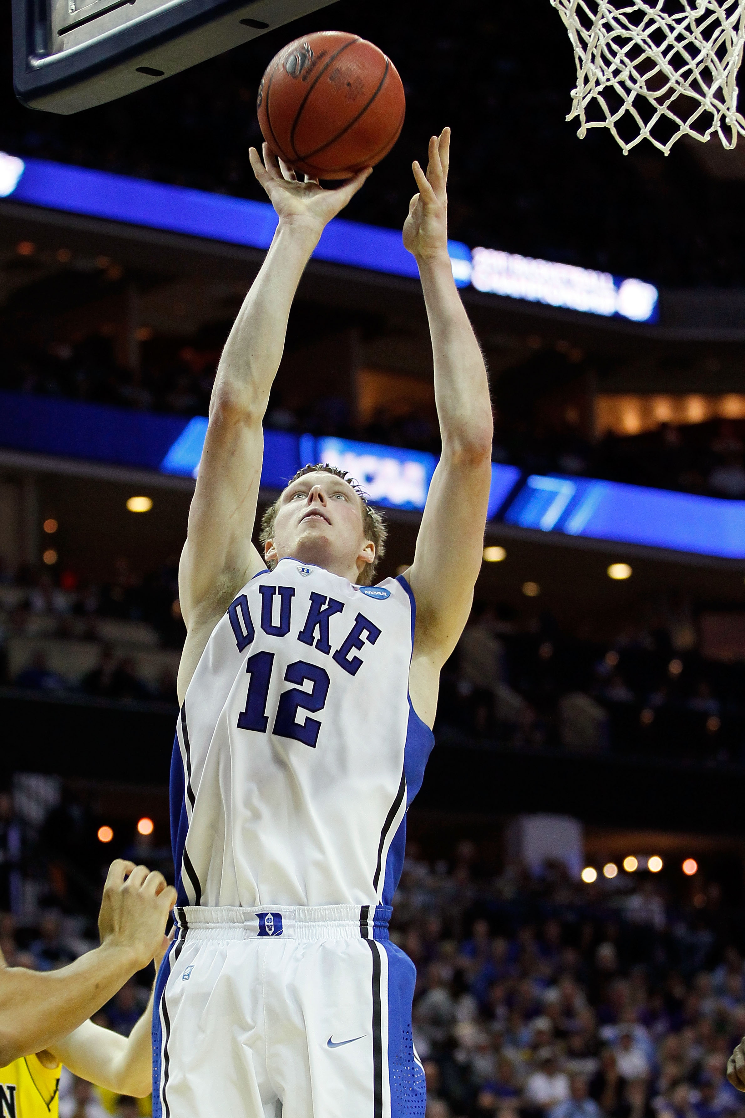 CHARLOTTE, NC - MARCH 20:  Kyle Singler #12 of the Duke Blue Devils lays the ball up while taking on the Michigan Wolverines during the third round of the 2011 NCAA men's basketball tournament at Time Warner Cable Arena on March 20, 2011 in Charlotte, Nor