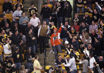 BOSTON, MA - MAY 06: A Philadelphia Flyers fan catches an errant puck amidst the Boston Bruins fans in Game Four of the Eastern Conference Semifinals during the 2011 NHL Stanley Cup Playoffs at TD Garden on May 6, 2011 in Boston, Massachusetts. The Bruins