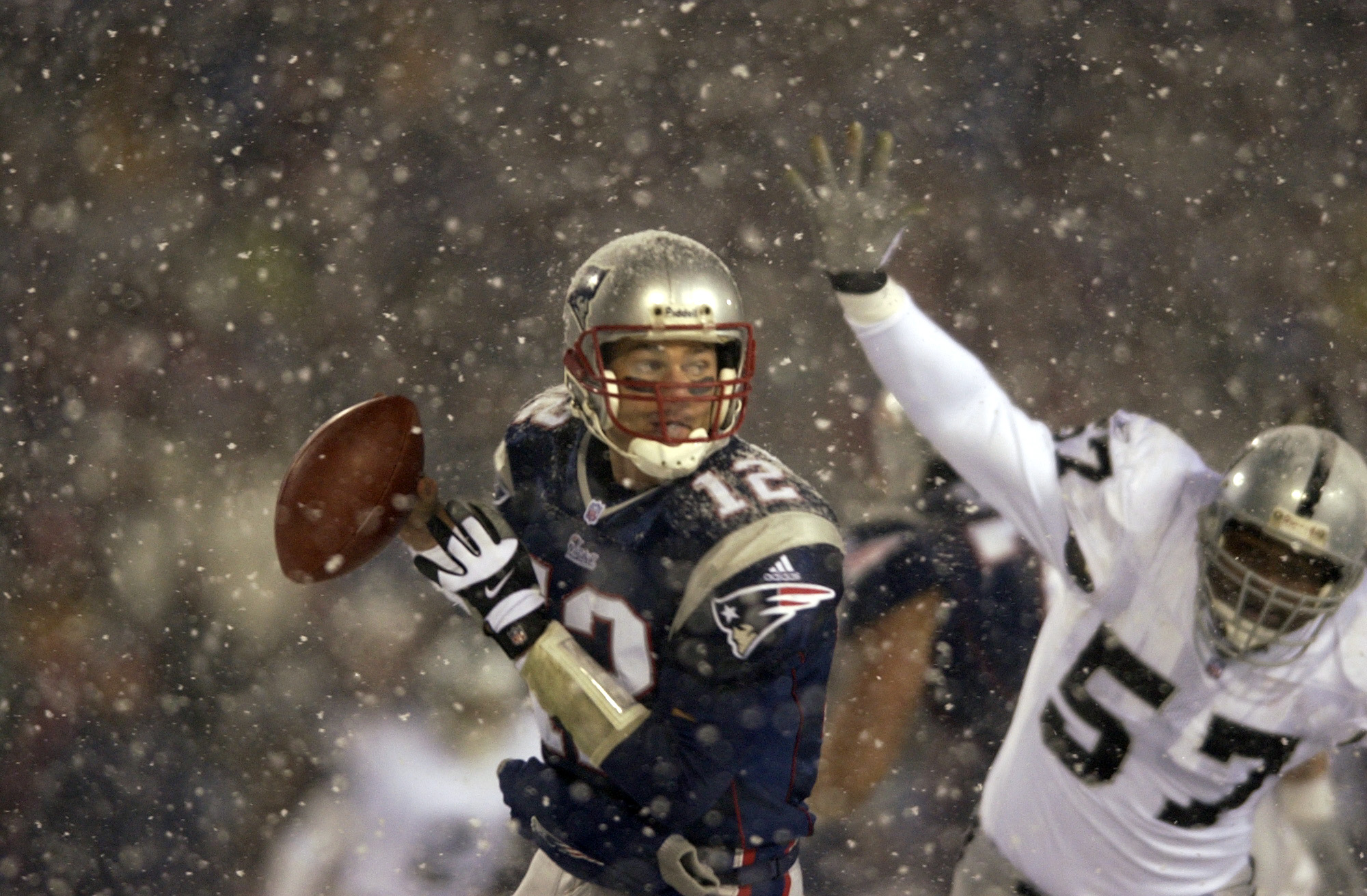 19 Jan 2002:  Quarterback Tom Brady #12 of the New England Patriots scrambles against the defense of Rod Coleman #57 of the Oakland Raiders during the AFC playoff game at Foxboro Stadium in Foxboro, Massachuesetts. The Patriots came from behind to win 16-