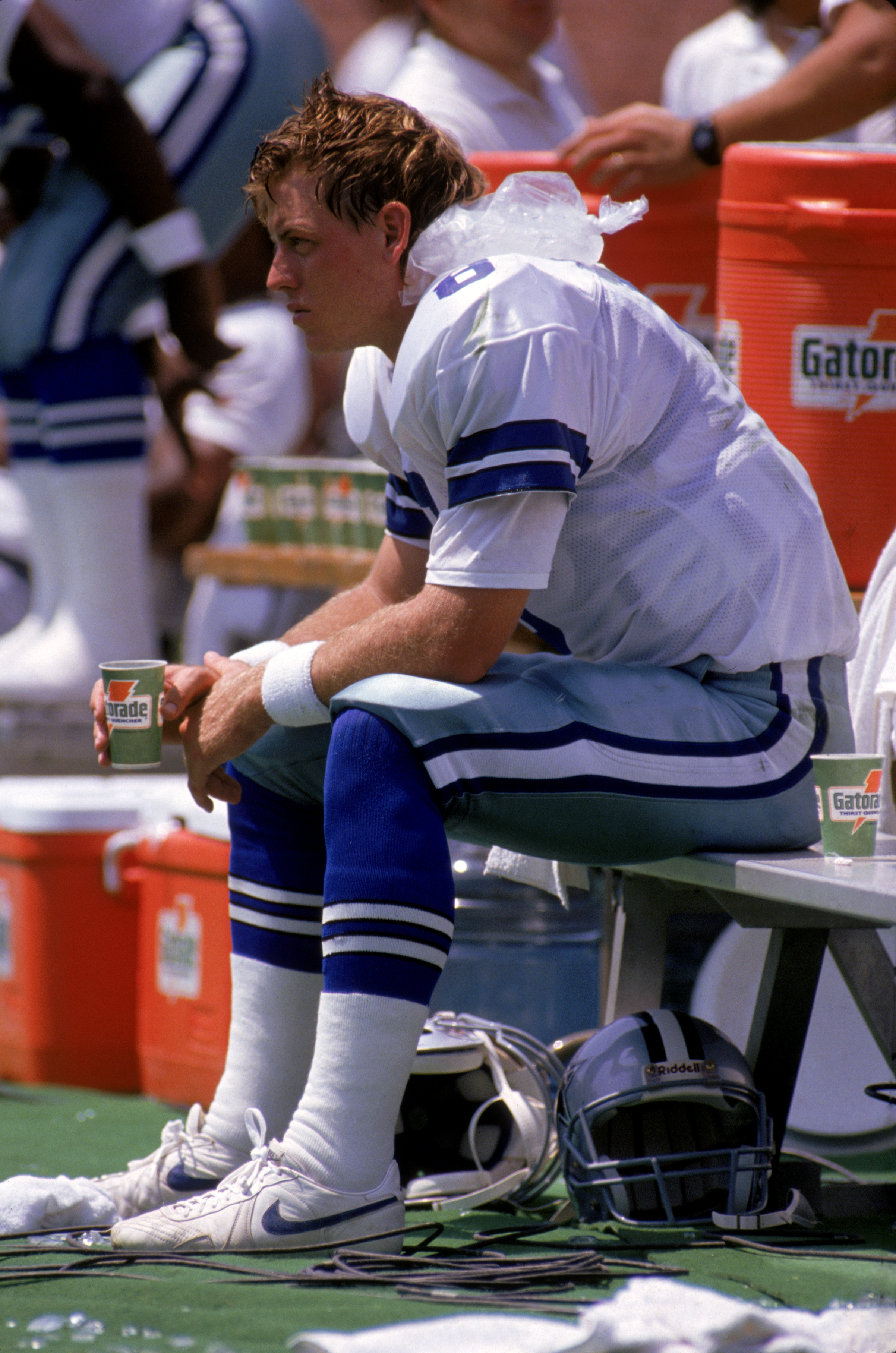 OAKLAND, CA - AUGUST 18:  Quarterback Troy Aikman #8 of the Dallas Cowboys ices the back of his neck and drinks a cup of Gatorade as he sits on the bench to recover from a concussion during a preseason game against the Oakland Raiders at Oakland/Alameda C