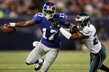 EAST RUTHERFORD, NJ - SEPTEMBER 30:  William James #21 of the Philadelphia Eagles tries to take down Plaxico Burress #17 of the New York Giants at Giants Stadium on September 30, 2007 in East Rutherford, New Jersey.  (Photo by Nick Laham/Getty Images)