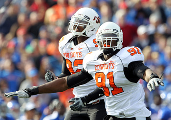 LAWRENCE, KS - NOVEMBER 20:  Ugo Chinasa #91 and Darius Hart #92 of the Oklahoma State Cowboys celebrate after the Cowboys stopped the Kansas Jayhawks from scoring at the goal line during the game on November 20, 2010 at Memorial Stadium in Lawrence, Kans
