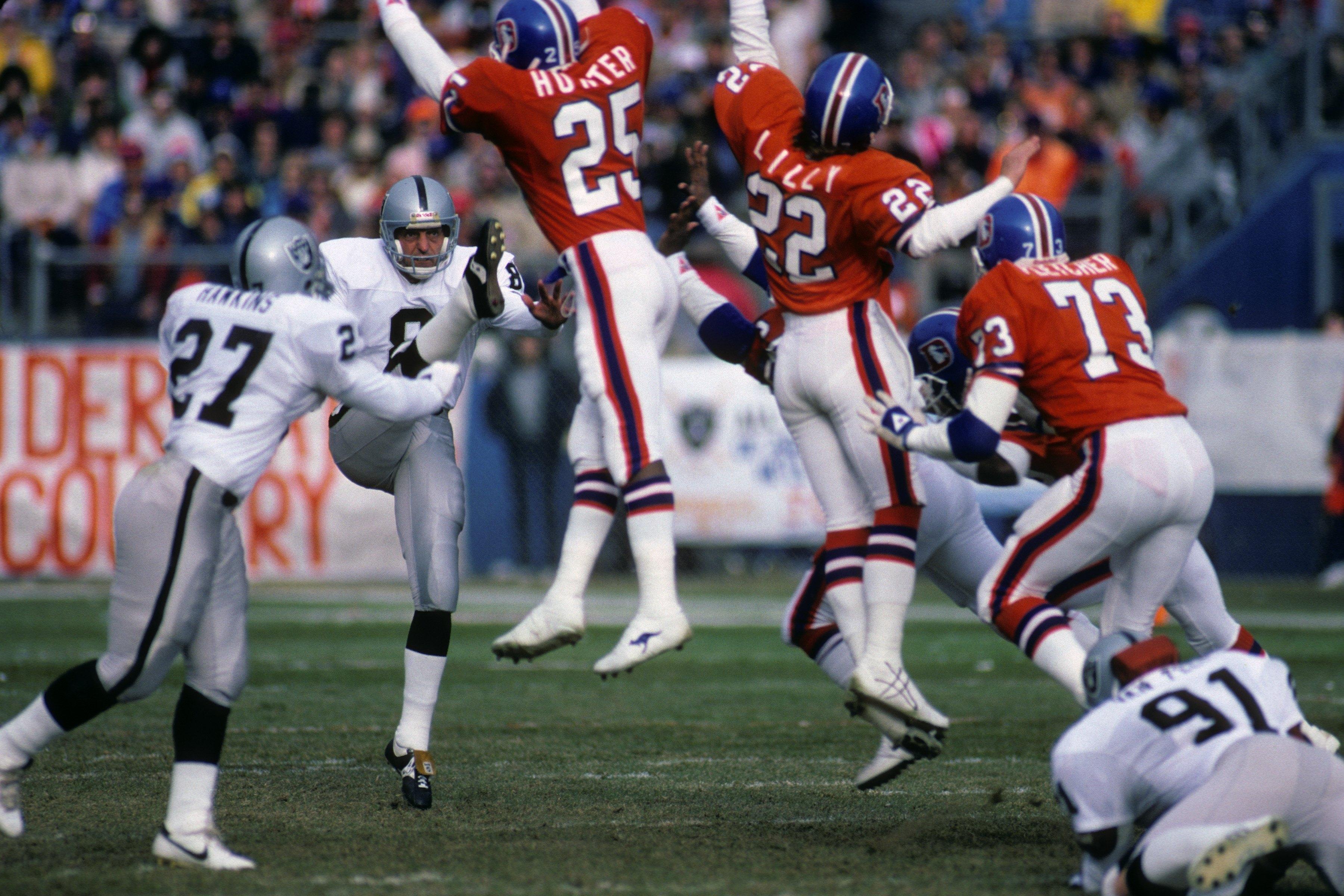DENVER - DECEMBER 8:  Punter Ray Guy #8 of the Los Angeles Raiders kicks the ball away against defensive backs Daniel Hunter #25, Tony Lilly #22 and linebacker Simon Fletcher #73 of the Denver Broncos during the game at Mile High Stadium on December 8, 19