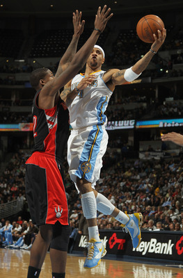 DENVER, CO - MARCH 21:  Kenyon Martin #4 of the Denver Nuggets lays up a shot against Ed Davis #32 of the Toronto Raptors at the Pepsi Center on March 21, 2011 in Denver, Colorado. The Nuggets defeated the Raptors 123-90. NOTE TO USER: User expressly ackn