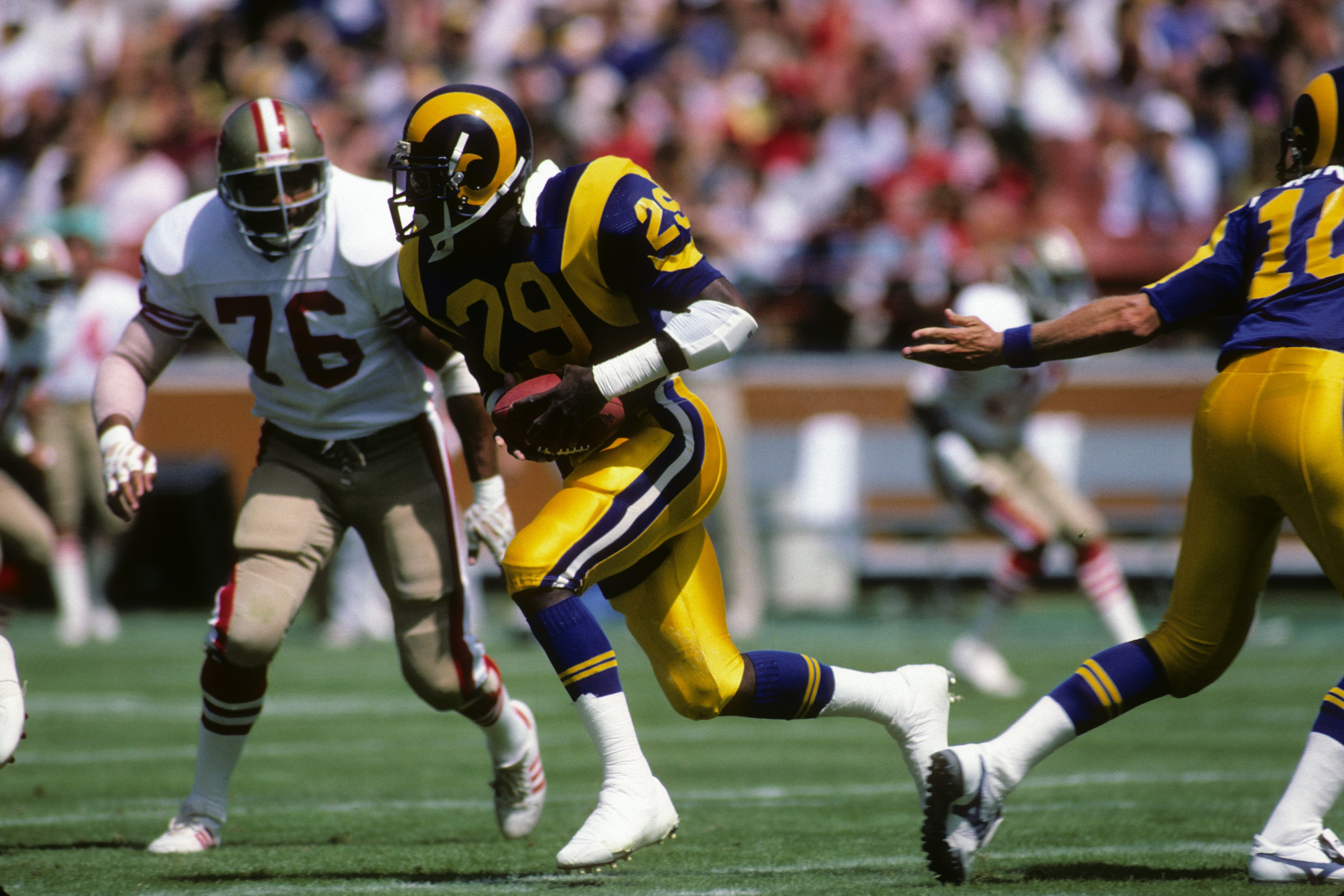 ANAHEIM, CA - SEPTEMBER 14:  Running back Eric Dickerson #28 of the Los Angeles Rams runs with the ball against defensive back Dwaine Board #76 of the San Francisco 49ers during the game at Anaheim Stadium on September 14, 1986 in Anaheim, California.   T