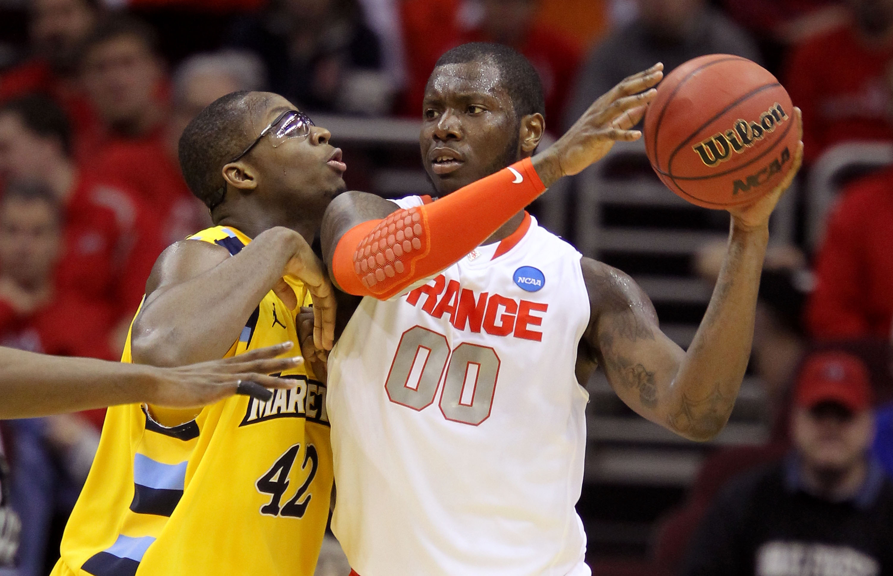CLEVELAND, OH - MARCH 20: Rick Jackson #00 of the Syracuse Orange handles the ball against Chris Otule #42 of the Marquette Golden Eagles during the third of the 2011 NCAA men's basketball tournament at Quicken Loans Arena on March 20, 2011 in Cleveland,