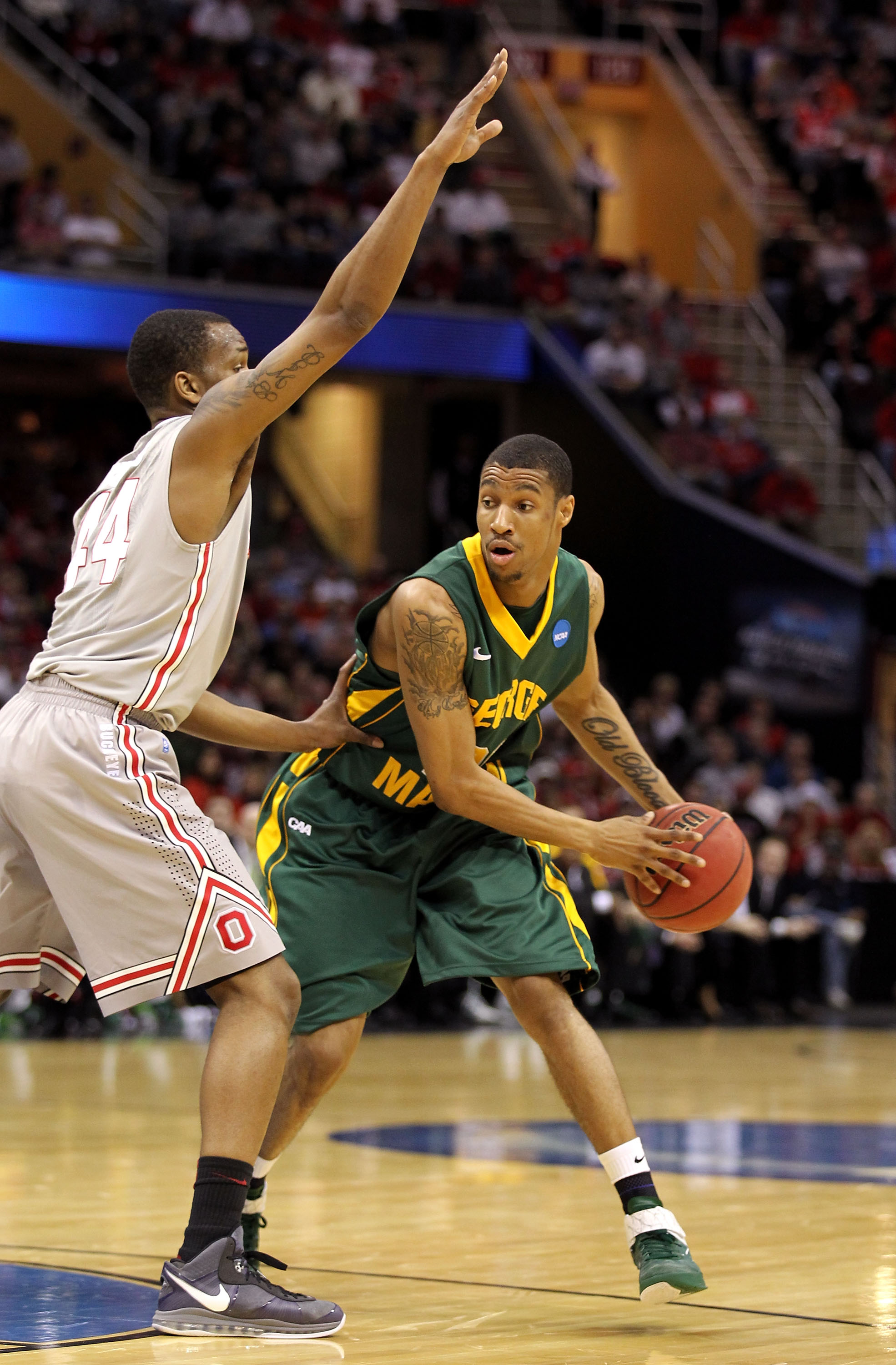 CLEVELAND, OH - MARCH 20: Cam Long #20 of the George Mason Patriots looks to pass against William Buford #44 of the Ohio State Buckeyes during the third of the 2011 NCAA men's basketball tournament at Quicken Loans Arena on March 20, 2011 in Cleveland, Oh