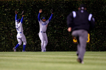 CHICAGO - OCTOBER 02:  (L-R) Juan Pierre #9 and Matt Kemp #27 of the Los Angeles Dodgers raise their arms towards the umpire as they lost the ball in the ivy on a ground rule double hit by Derrek Lee #25 of the Chicago Cubs in Game Two of the NLDS during