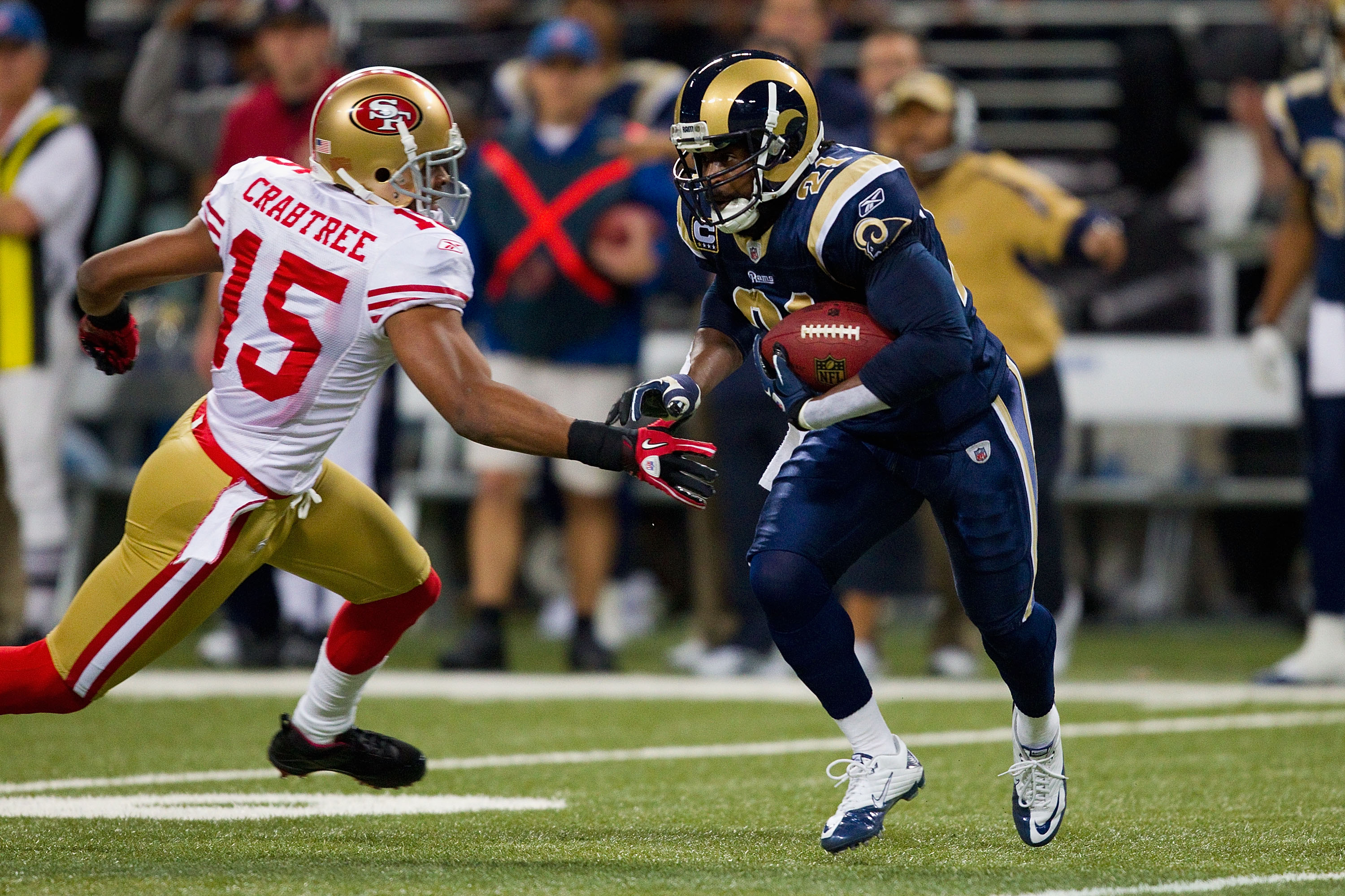 ST. LOUIS, MO - DECEMBER 26: Oshiomogho Atogwe #21 of the St. Louis Rams returns an interception against Michael Crabtree #15 of the San Francisco 49ers at the Edward Jones Dome on December 26, 2010 in St. Louis, Missouri. The Rams beat the 49ers 25-17. (