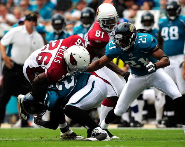 JACKSONVILLE, FL - SEPTEMBER 20:  Beanie Wells #26 is tackked by Reggie Nelson #25 of the Jacksonville Jaguars during the game at Jacksonville Municipal Stadium on September 20, 2009 in Jacksonville, Florida.  (Photo by Sam Greenwood/Getty Images)
