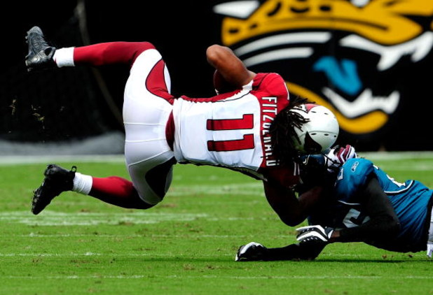 JACKSONVILLE, FL - SEPTEMBER 20:  Larry Fitzgerald #11 of the Arizona Cardinals is tackled by Reggie Nelson #25 of the Jacksonville Jaguars during the game at Jacksonville Municipal Stadium on September 20, 2009 in Jacksonville, Florida.  (Photo by Sam Gr