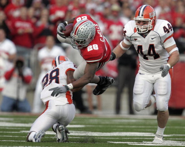COLUMBUS - NOVEMBER 10:  Chris Wells #28 of the Ohio State Buckeyes is tackled by Dere Hicks #28 of the Illinois Fighting Illini as Illinois player Brit Miller #44 looks on during the first quarter at Ohio Stadium November 10, 2007 in Columbus, Ohio. Illi