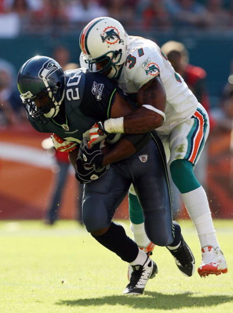 MIAMI - NOVEMBER 09:  Running back Maurice Morris #20 of the Seattle Seahawks is brought down by safety Yeremiah Bell #37 of the Miami Dolphins at Dolphin Stadium on November 9, 2008 in Miami, Florida. The Dolphins defeated the Seahawks 21-19.  (Photo by