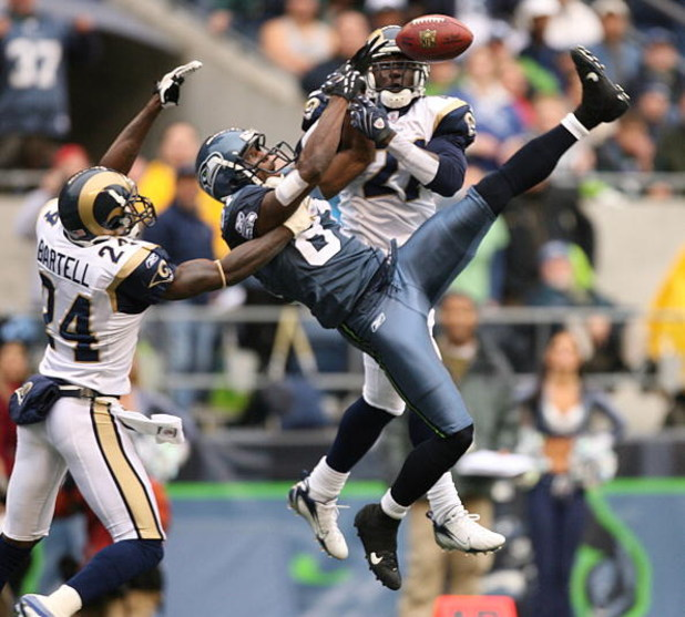 SEATTLE - OCTOBER 21:  Wide receiver Nate Burleson #81 of the Seattle Seahawks leaps for a pass that fell incomplete against Ron Bartell #24 and Oshiomogho Atogwe #21 of the St. Louis Rams at Qwest Field October 21, 2007 in Seattle, Washington. The Seahaw