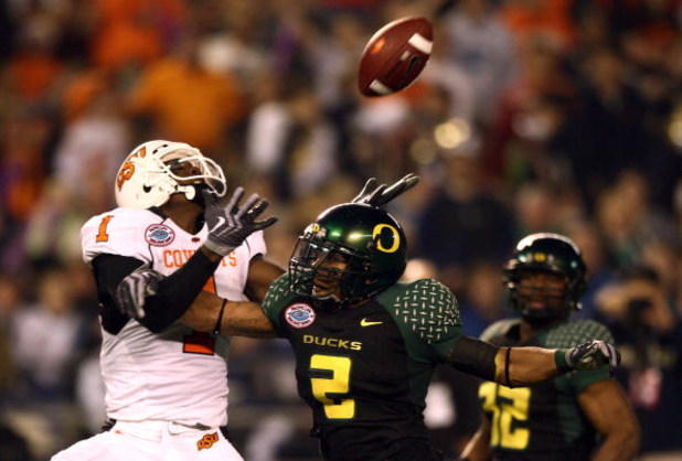 SAN DIEGO, CA - DECEMBER 30:   Wide Receiver Dez Bryant  #1 of the Oklahoma State University Cowboys jumps up to catch the ball as Free Safety T.J. Ward #2 of the University of Oregon Ducks breaks up the pass during the Pacific Life Holiday Bowl at Qualco