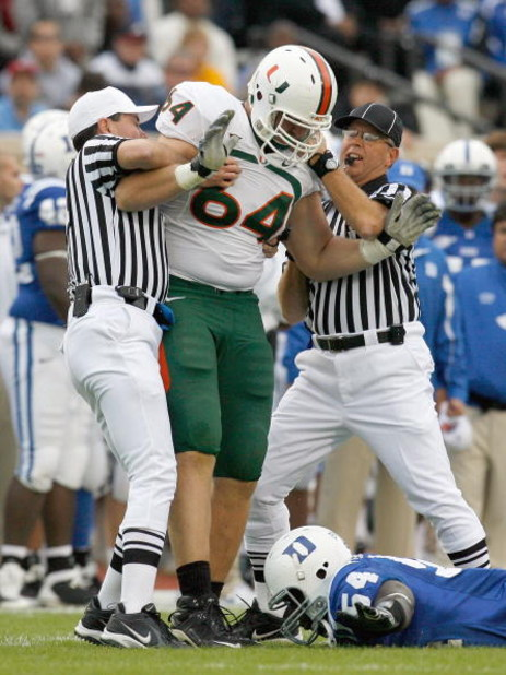 DURHAM, NC - OCTOBER 18:  Greg Akinbiyi #54 of the Duke Blue Devils lays on the ground as referees pull Jason Fox #64 of the Miami Hurricanes off him during the game at Wallace Wade Stadium on October 18, 2008 in Durham, North Carolina.  (Photo by Kevin C