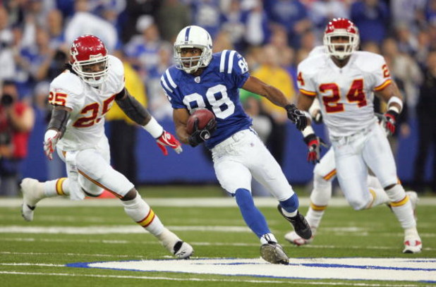 INDIANAPOLIS - JANUARY 06:  Marvin Harrison #88 of the Indianapolis Colts runs for yards after the catch on a 42-yard reception in the first quarter against Lenny Walls #25 and Ty Law #24 of the Kansas City Chiefs during their AFC Wild Card Playoff Game J