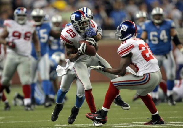 DETROIT - NOVEMBER 18:  Sam Madison #29 of the New York Giants makes an interception in front of Gibril Wilson #29 as he is tackled by Shaun McDonald #84 of the Detroit Lions during the fourth quarter at Ford Field on November 18, 2007 in Detroit, Michiga