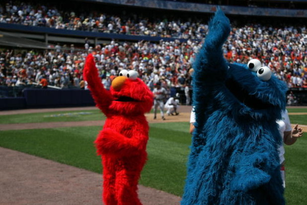 NEW YORK - AUGUST 09:  Sesame Street's Elmo and Cookie Monster mascots wave to fans the first 'Mets Shoelace Day' at Shea Stadium on August 9, 2007 in the Queens borough of New York City.  (Photo by Bryan Bedder/Getty Images)