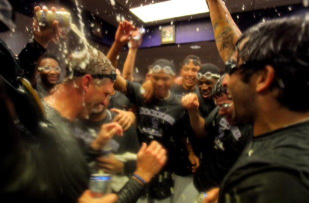 DENVER - OCTOBER 01:  Manager Jim Tracy (L) of the Colorado Rockies is showered by his teammates as they celebrate in the clubhouse after they defeated the Milwaukee Brewers 9-2 and clinched a National League playoff berth at Coors Field on October 1, 200