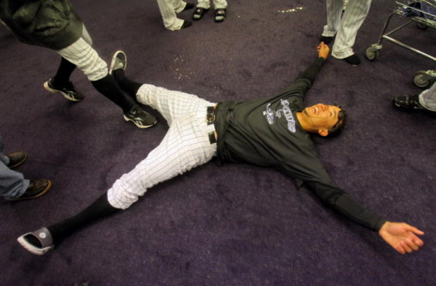 DENVER - OCTOBER 01:  Carlos Gonzalez of the Colorado Rockies lays on the floor as the Rockies celebrate in the clubhouse after they defeated the Milwaukee Brewers 9-2 and clinched a National League playoff berth at Coors Field on October 1, 2009 in Denve