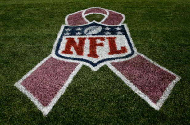 DENVER - OCTOBER 04:  The NFL logo is adorned with a pink ribbon on the sidelines as part of a program to raise awareness for breast cancer as the Dallas Cowboys face the Denver Broncos during NFL action at Invesco Field at Mile High on October 4, 2009 in