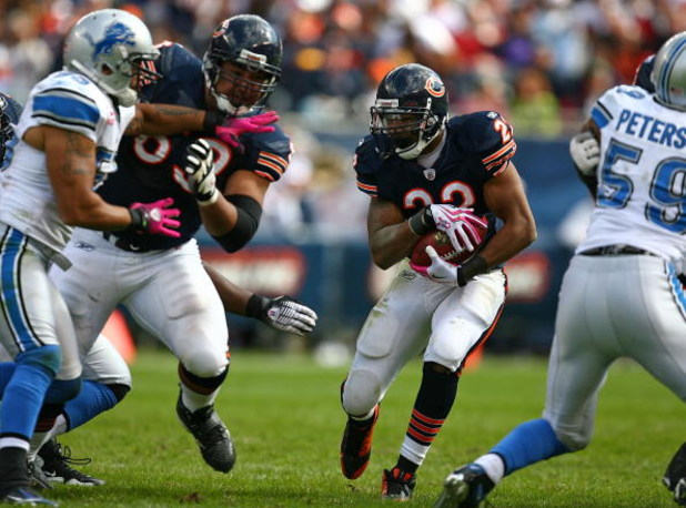 CHICAGO - OCTOBER 04: Matt Forte #22 of the Chicago Bears looks for running room as teammate Roberto Garza #63 blocks Larry Foote #55 of the Detroit Lions on October 4, 2009 at Soldier Field in Chicago, Illinois. The Bears defeated the Lions 48-24. (Photo