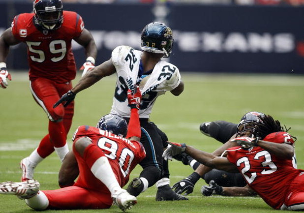HOUSTON - SEPTEMBER 27:  Running back Maurice Drew-Jones #32 of the Jacksonville Jaguars is brought down from behind by defensive end Mario Williams #90 of the Houston Texans in the fourth quarter at Reliant Stadium on September 27, 2009 in Houston, Texas