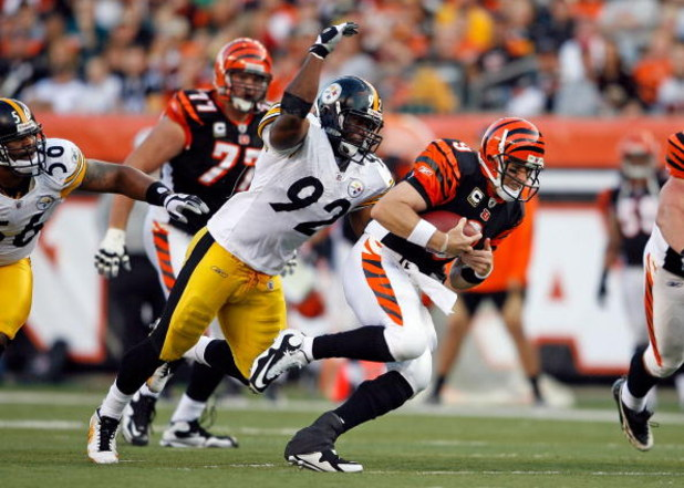 CINCINNATI - SEPTEMBER 27:  Carson Palmer #9 of the Cincinnati Bengals runs with the ball while defended by James Harrison #92 of the Pittsburgh Steelers at Paul Brown Stadium on September 27, 2009 in Cincinnati, Ohio.  The Bengals won 23-20.  (Photo by A